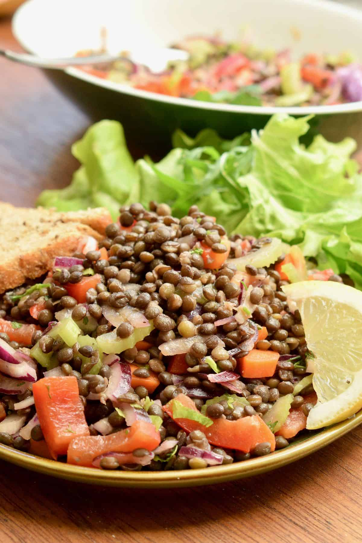 A pile of lentil salad on a plate, served with green salad and bread