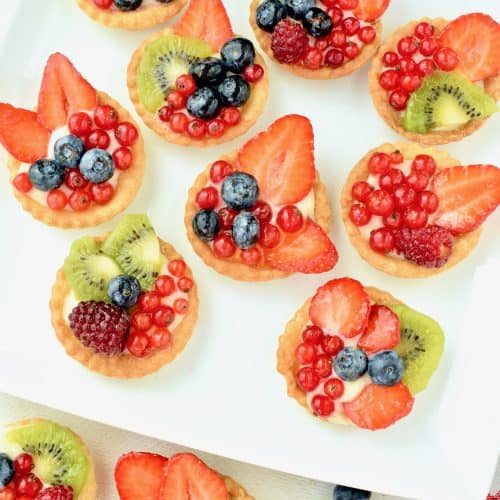 Some mixed fruit custard tarts served on a white plate. The topping is a colourful mix of fruit.