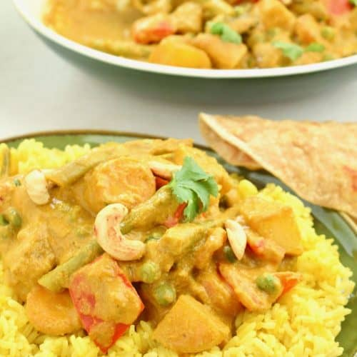A serving of veggie korma on top of a pile of Indian spiced rice