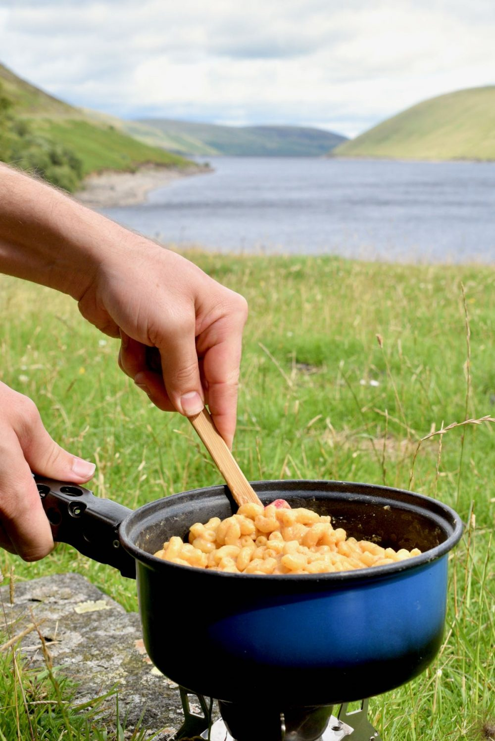 Cooking the mac and cheese on a camping stove. Hills and a lake in the background.