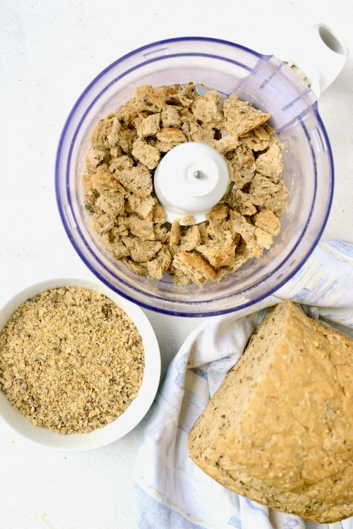 A food processor bowl containg bread cubes, next to a loaf of bread and bowl of breadcrumbs.