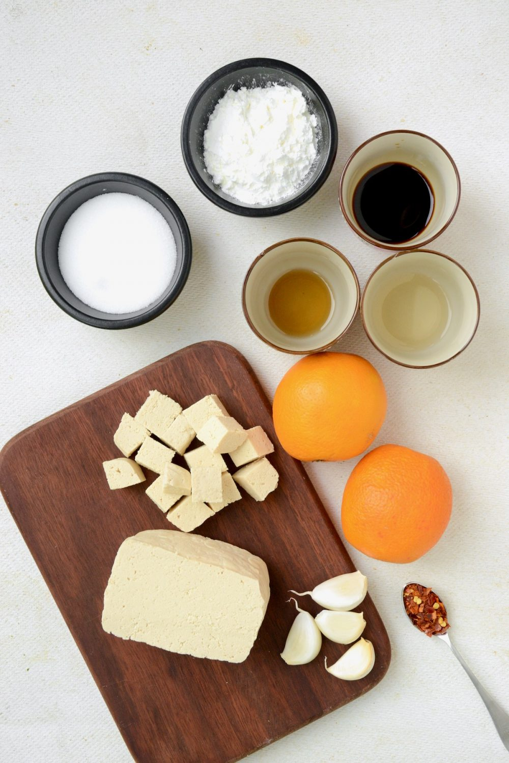 The ingredients that you will need if you want to make this recipe for orange tofu: A block of firm tofu, two medium oranges, garlic, sesame oil, soy sauce, rice vinegar, sugar and cornstarch. Chili flakes are an optional addition.