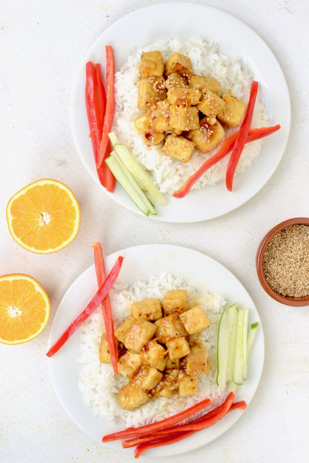 Two servings of Orange Tofu with white rice and raw vegetables, next to two orange halves and a small pot of toasted sesame seeds viewed from above.