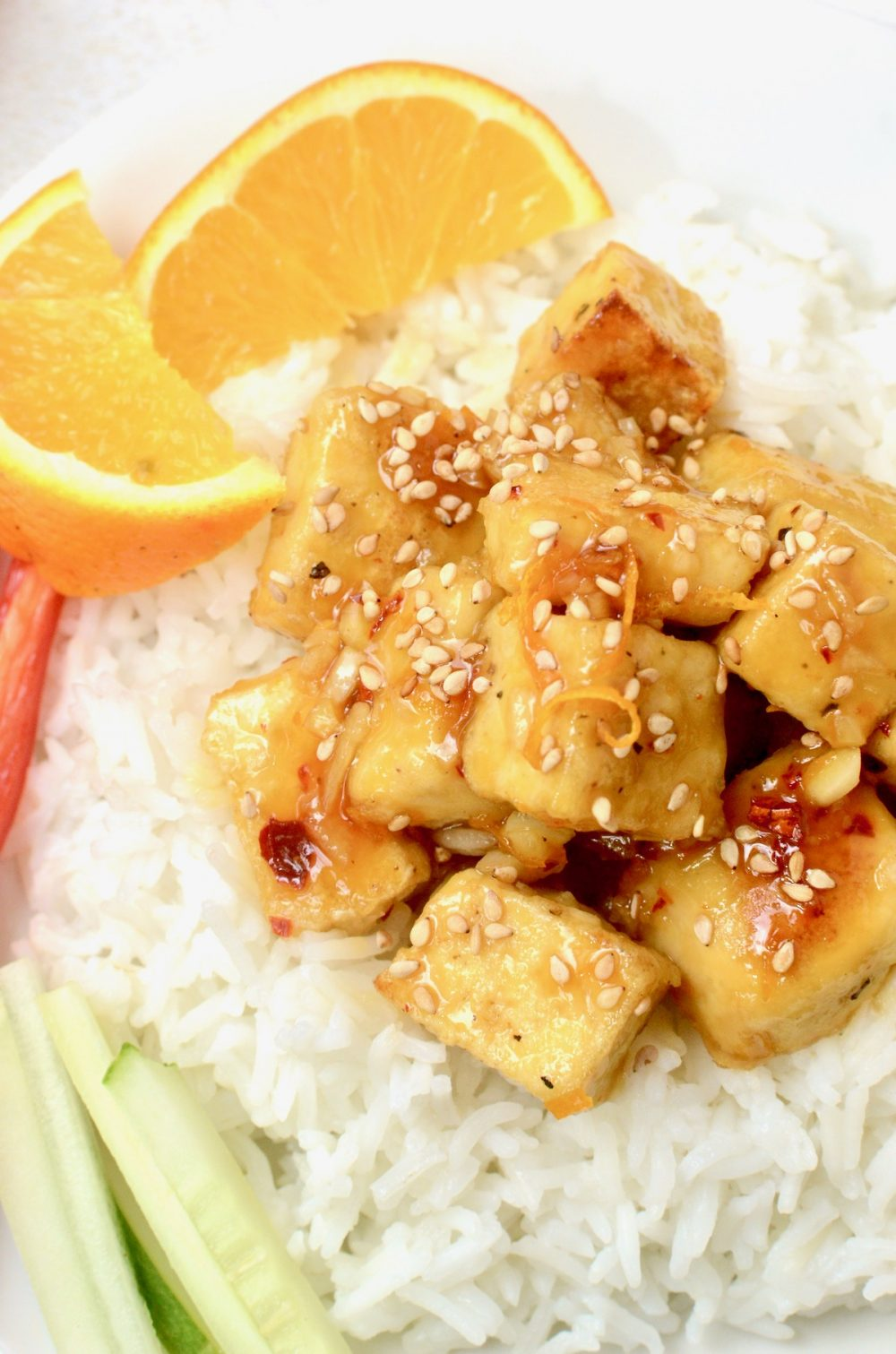 A close up shot of orange tofu sprinkled with toasted sesame seeds, served on white rice and with a wedge of fresh orange and raw vegetables.