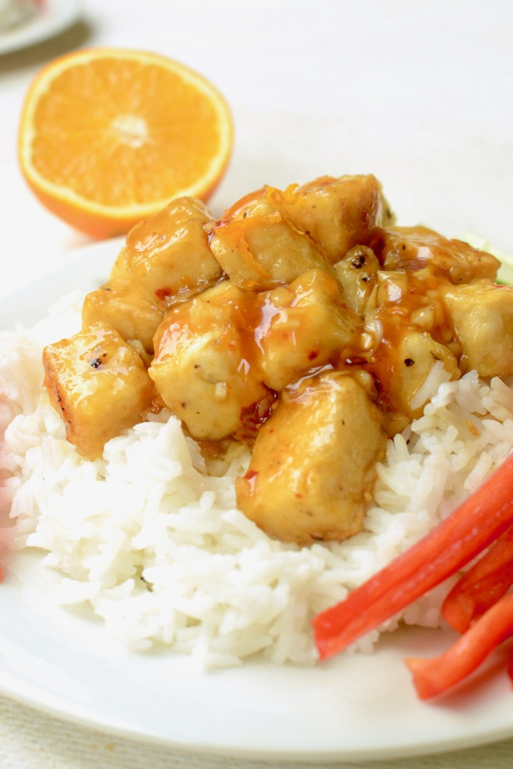A portion of orange tofu, coated thickly in sauce and served with some white rice alongside some fresh vegetables. A half orange in the background.