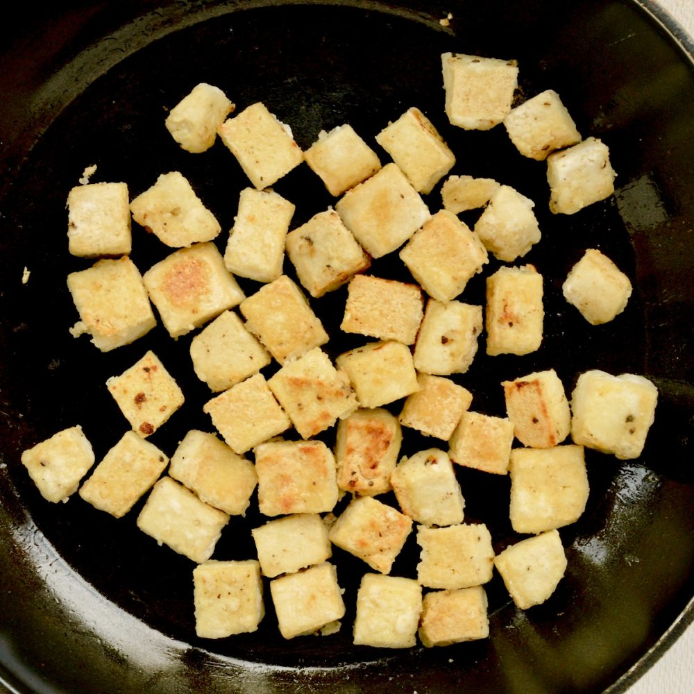 The coated tofu cubes are fried until golden brown and slightly crisp.