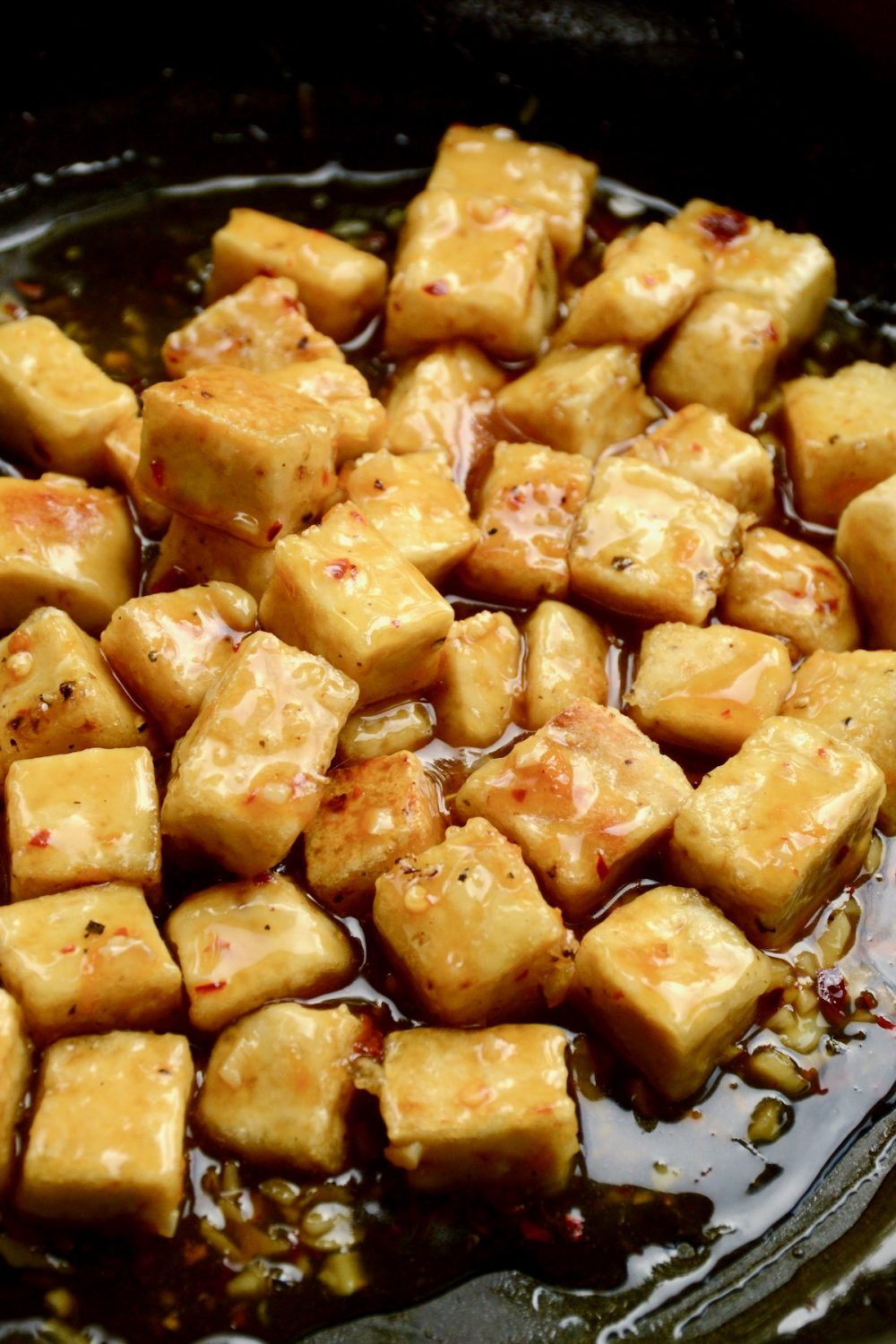 The fried tofu cubes have been added back into the pan and coated in the orange sauce.