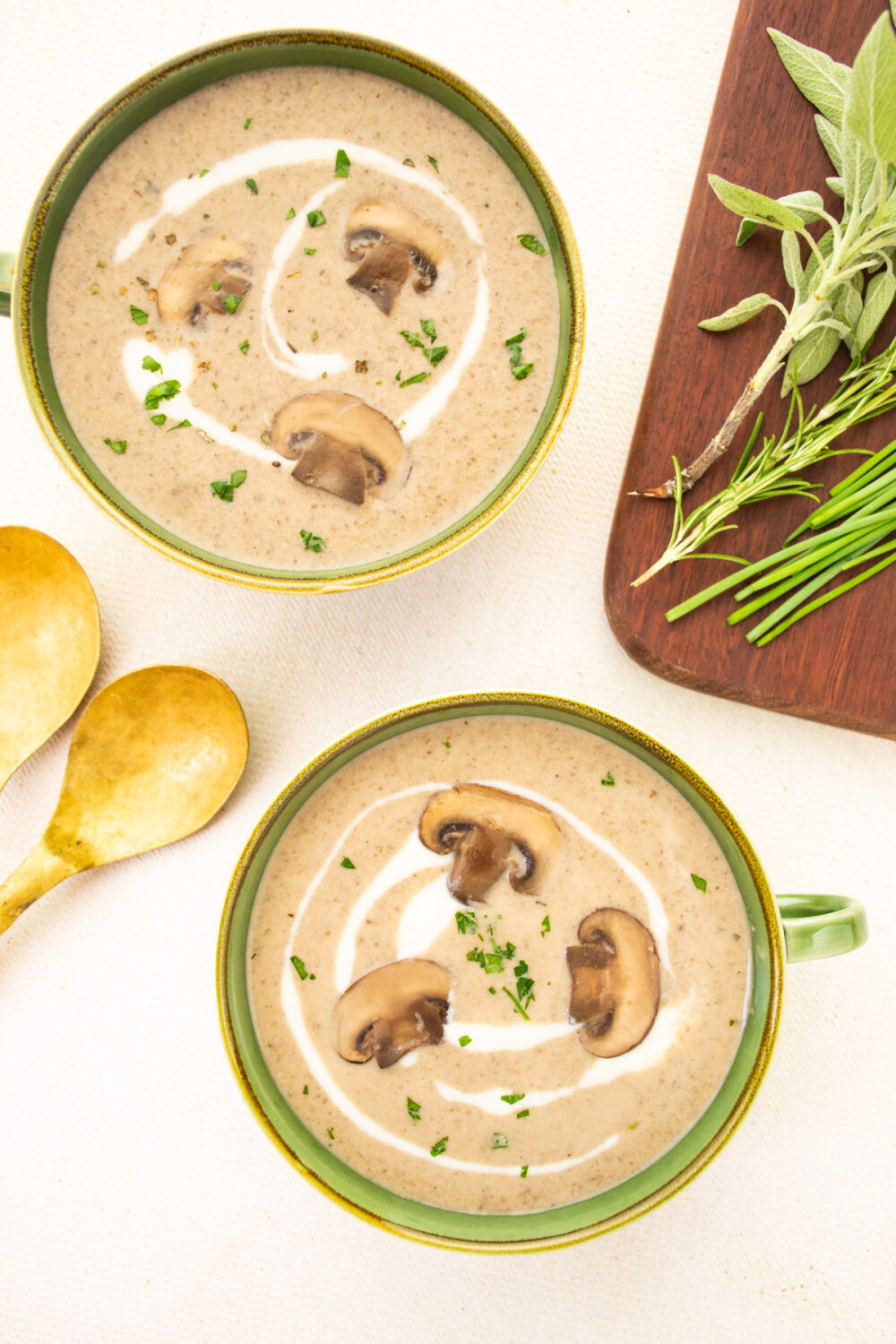 Two green bowls of mushroom soup, next to a board of herbs.