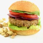 A nut burger with lettuce, tomato, red onion and cucumber in a burger bun. Some nuts are scattered around the burger.