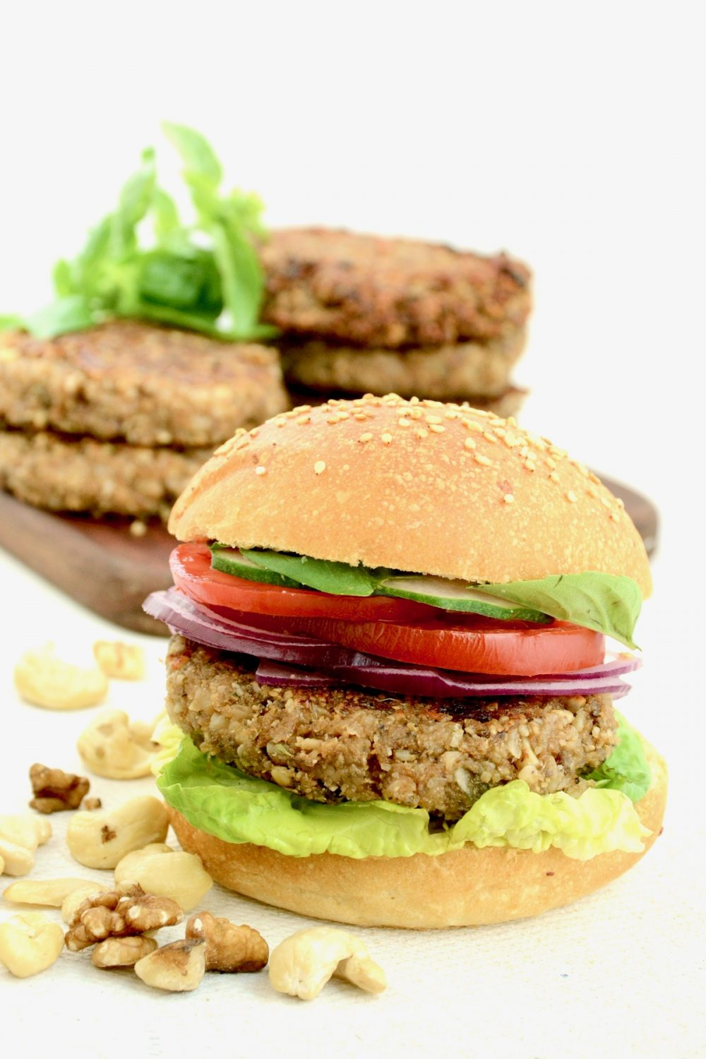 A nut burger with lettuce, tomato, red onion and cucumber in a burger bun. More nut patties are stacked in the background.
