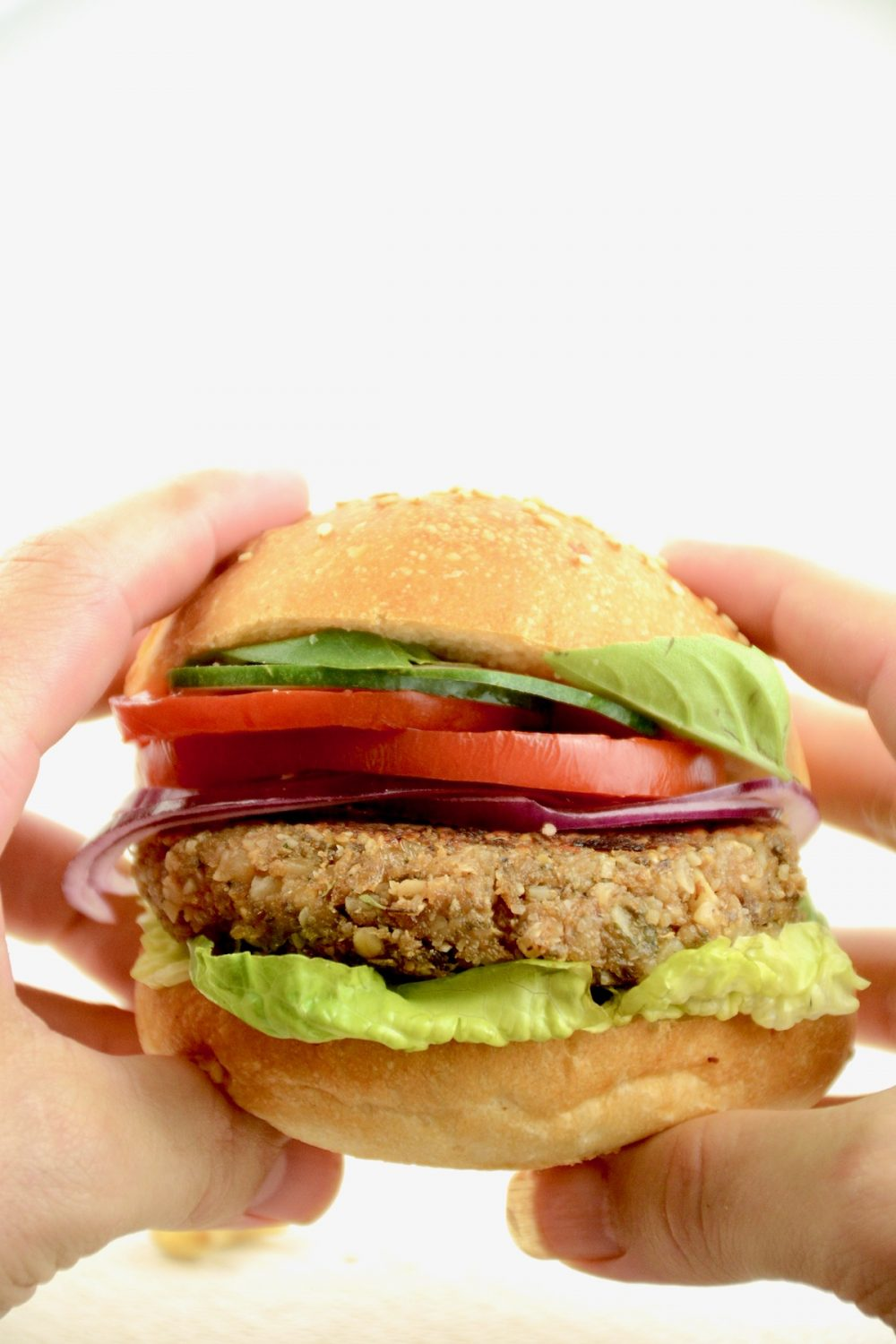 Hands holding up a burger in a bun. Apart from the nut patty, it is filled with lettuce and slices of tomato and red onion.