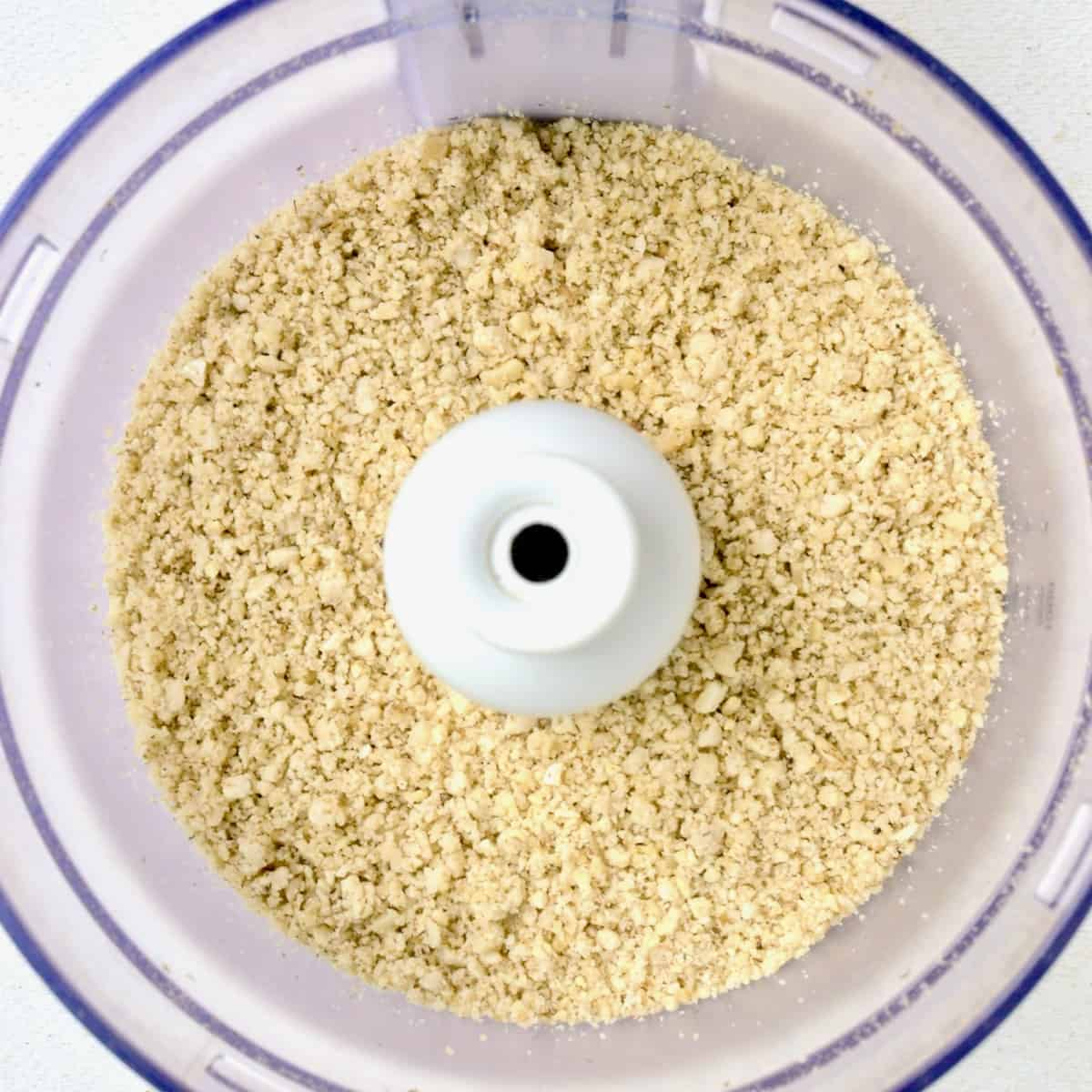 The mixed nuts have been ground to a slightly grainy texture in a food processor.