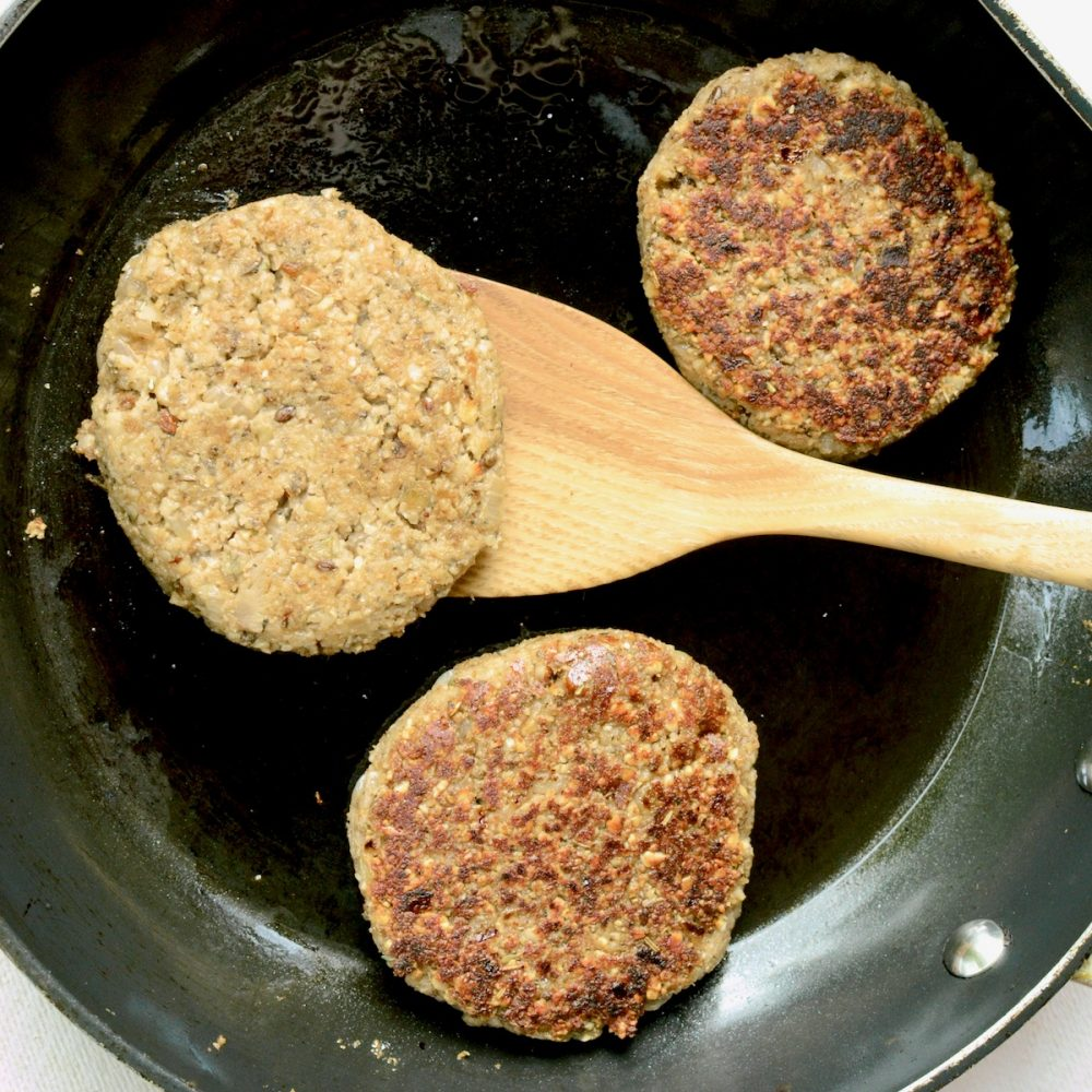 Three nut burgers cooking in a frying pan. One burger is about to be turned over, the other two show a slightly crispy and brown cooked top.