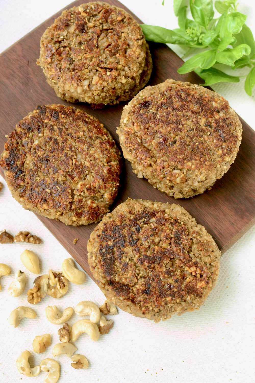 Some cooked nut burgers on a dark wooden board, with some fresh green leafs and nuts scattered around it.