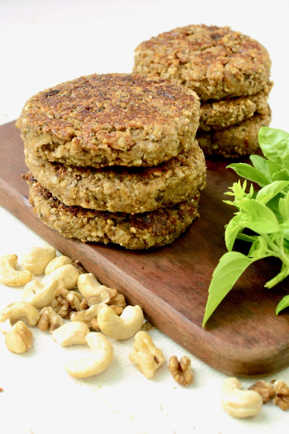 Some cooked nut burgers stacked on a dark wooden board.