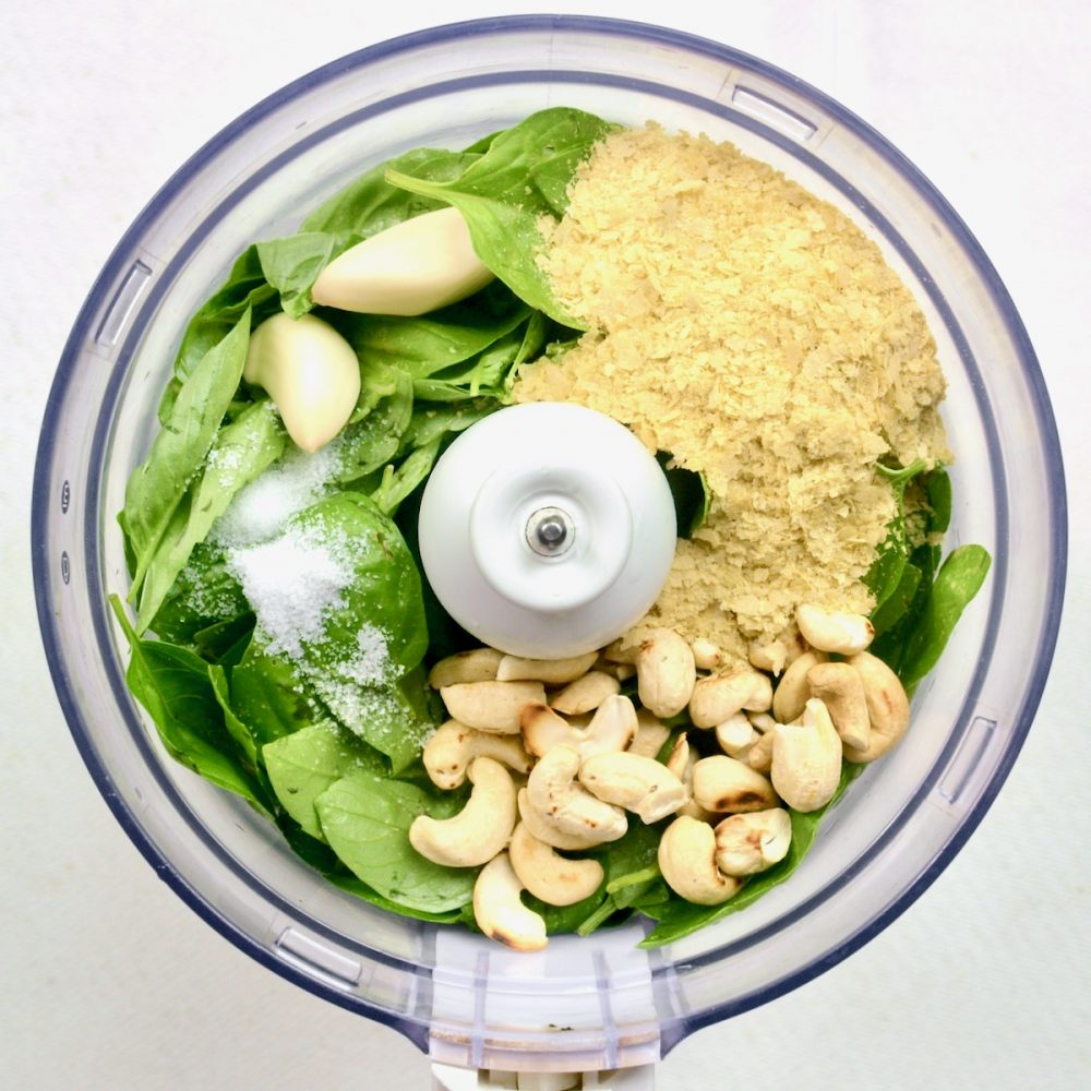 Viewed from above, the ingredients for the pesto have been added to a food processor and are ready for blending: Fresh basil and garlic, nutritional yeast flakes, toasted cashew nuts and some salt.