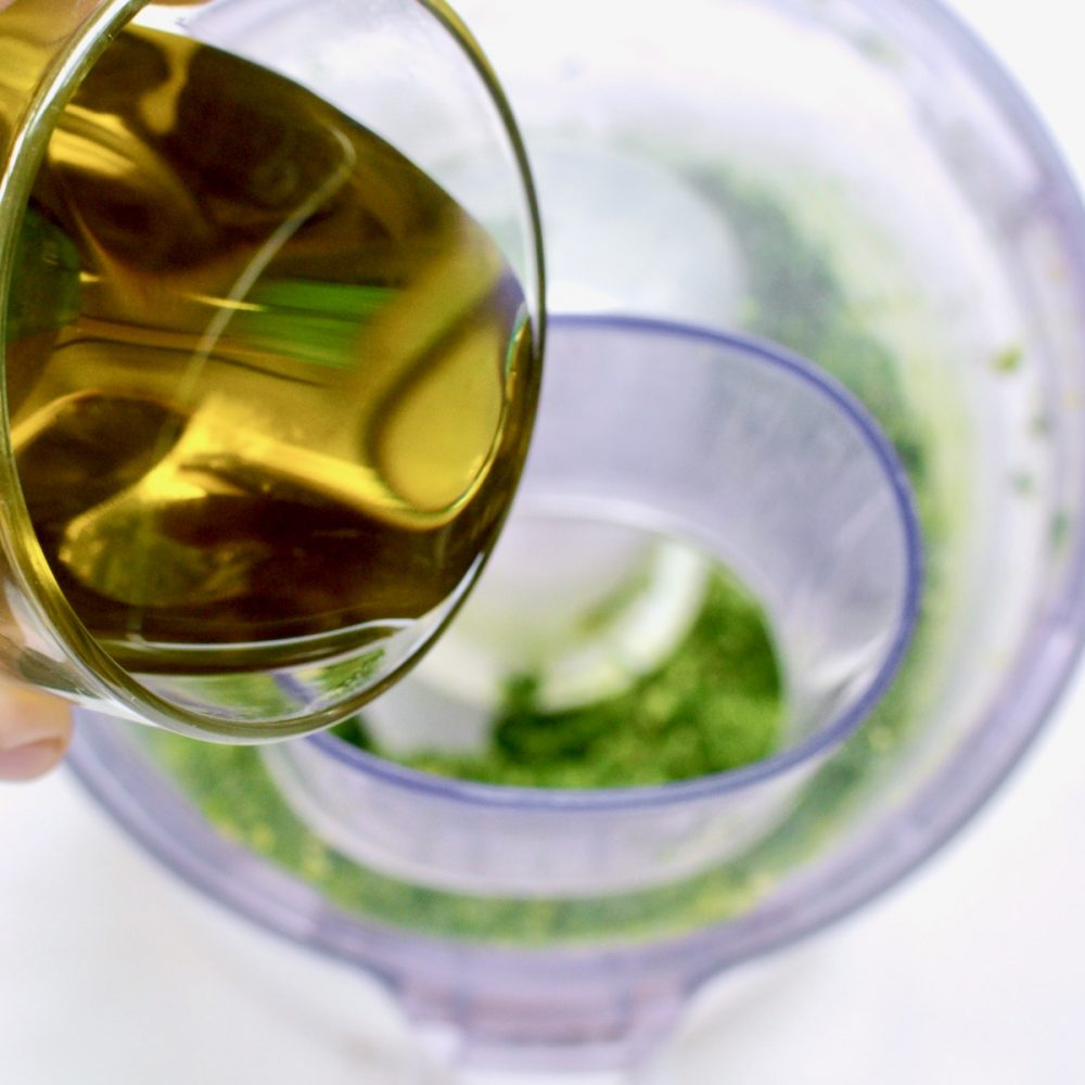 From a glass olive oil is poured into a food processor where pesto is blended.