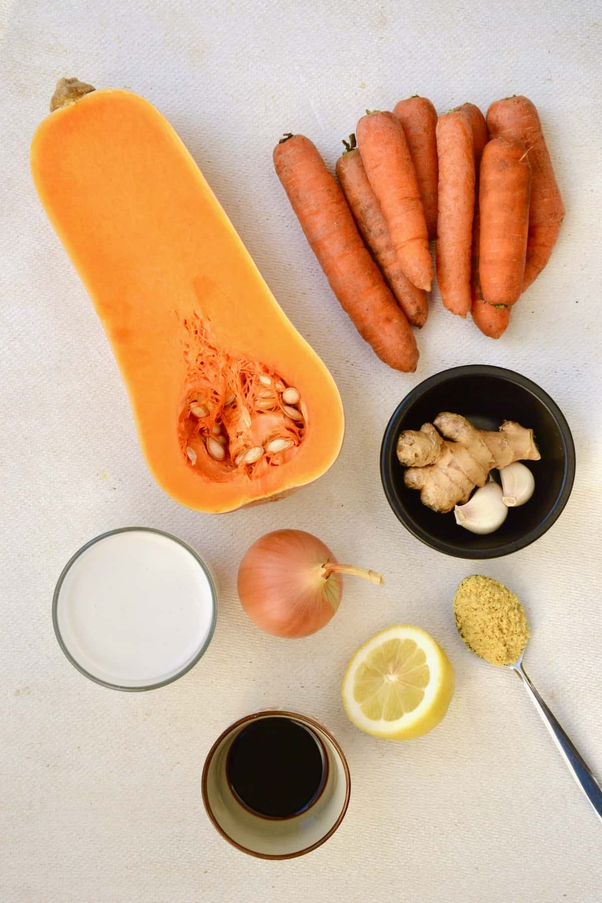 Soup ingredients - a half butternut squash, some carrots, ginger and garlic in a dish, coconut milk, soy sauce, an onion, half a lemon and a spoonful of stock powder.