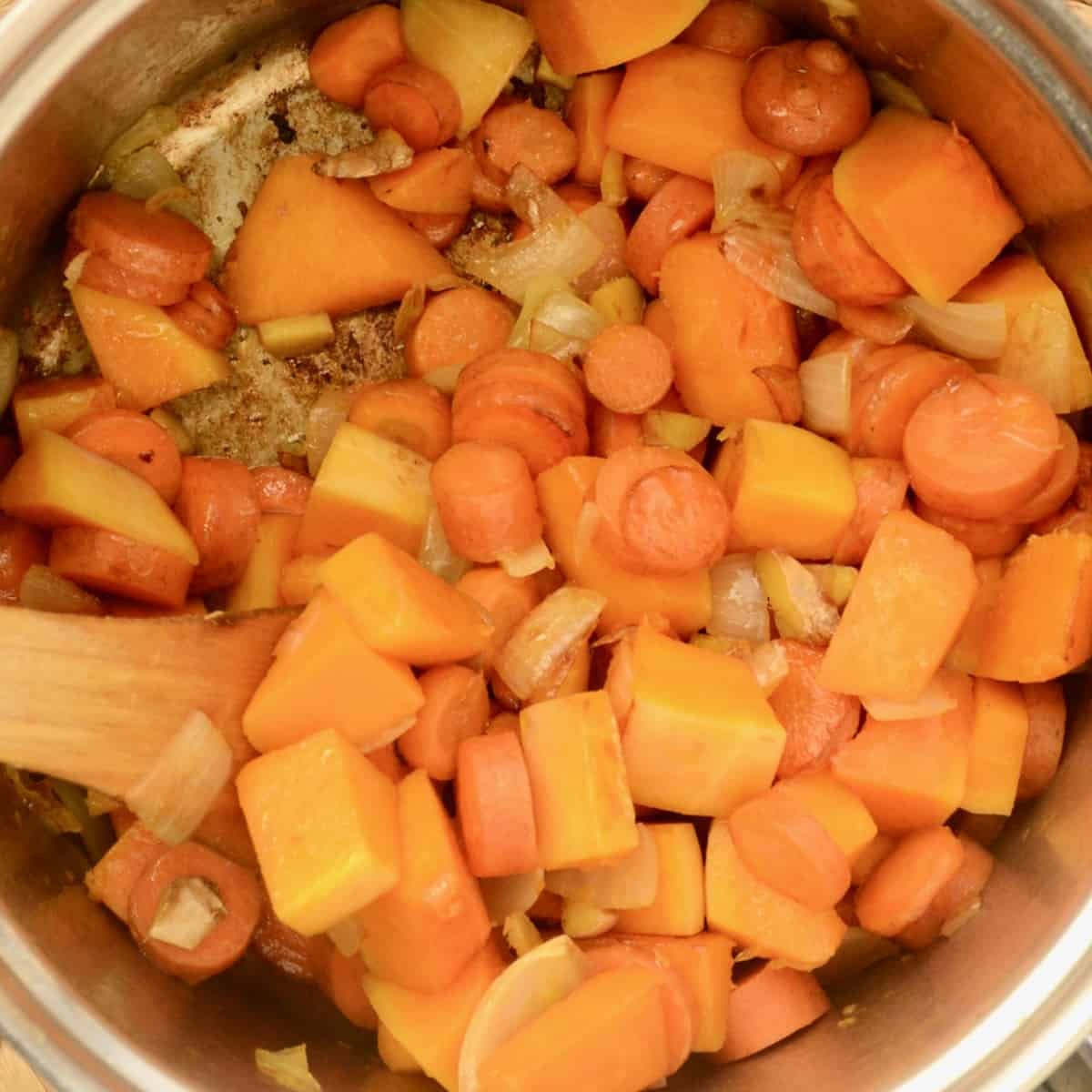 Chunks of squash, carrots, onion and ginger browning in a saucepan.