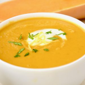 A white bowl of butternut squash soup.
