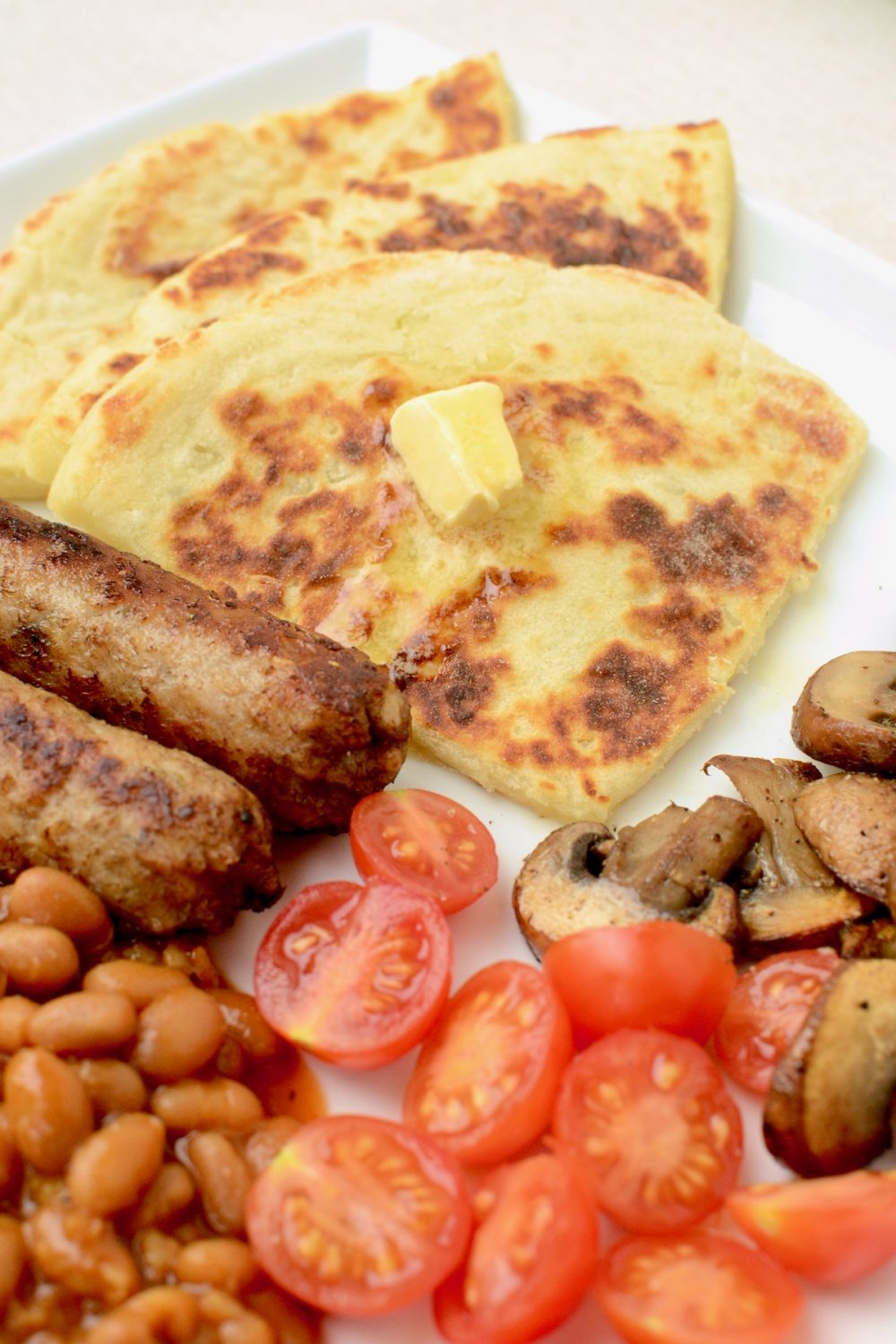 Tatty scones with butter as part of a fully vegan Breakfast: There are vegan sausages, baked beans, cherry tomatoes and fried mushrooms.