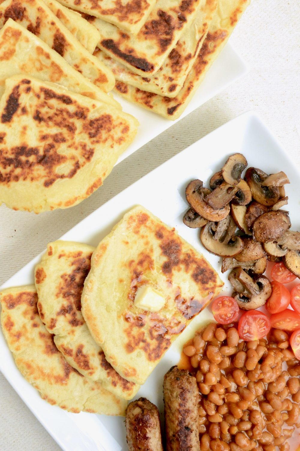 A breakfast plate of potato scones with butter, vegan sausages, baked beans, tomatoes and mushrooms. On its side a plate with more of the browned cooked tatty scones.