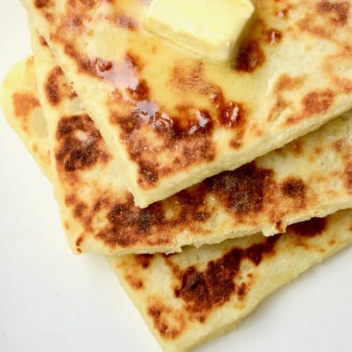 On top of three stacked potato scones, a square of vegan butter alternative. It is melting on the warm scone and slowly spreading on the crusty brown surface.