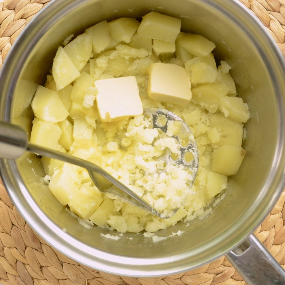 Potatoes being mashed in a saucepan while butter is incorporated in the same step..
