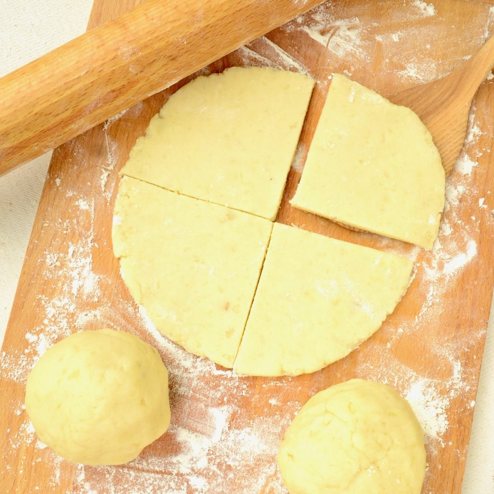 On a wooden board, a rolled circle of potato dough is cut in two. One quarter is lifted up by a wooden spatula. More dough is waiting to be rolled out.