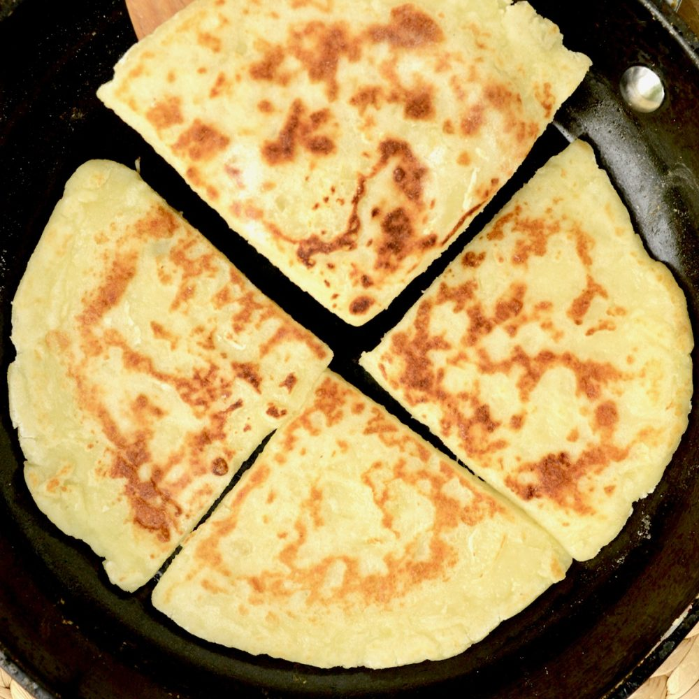 Four cooked tatty scones in a frying pan. Their surface is sprinkled with brown, crusty parts.