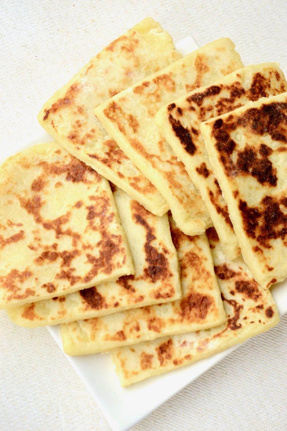 Potato scones beautifully arranged like fallen dominoes in two lines on a white plate.