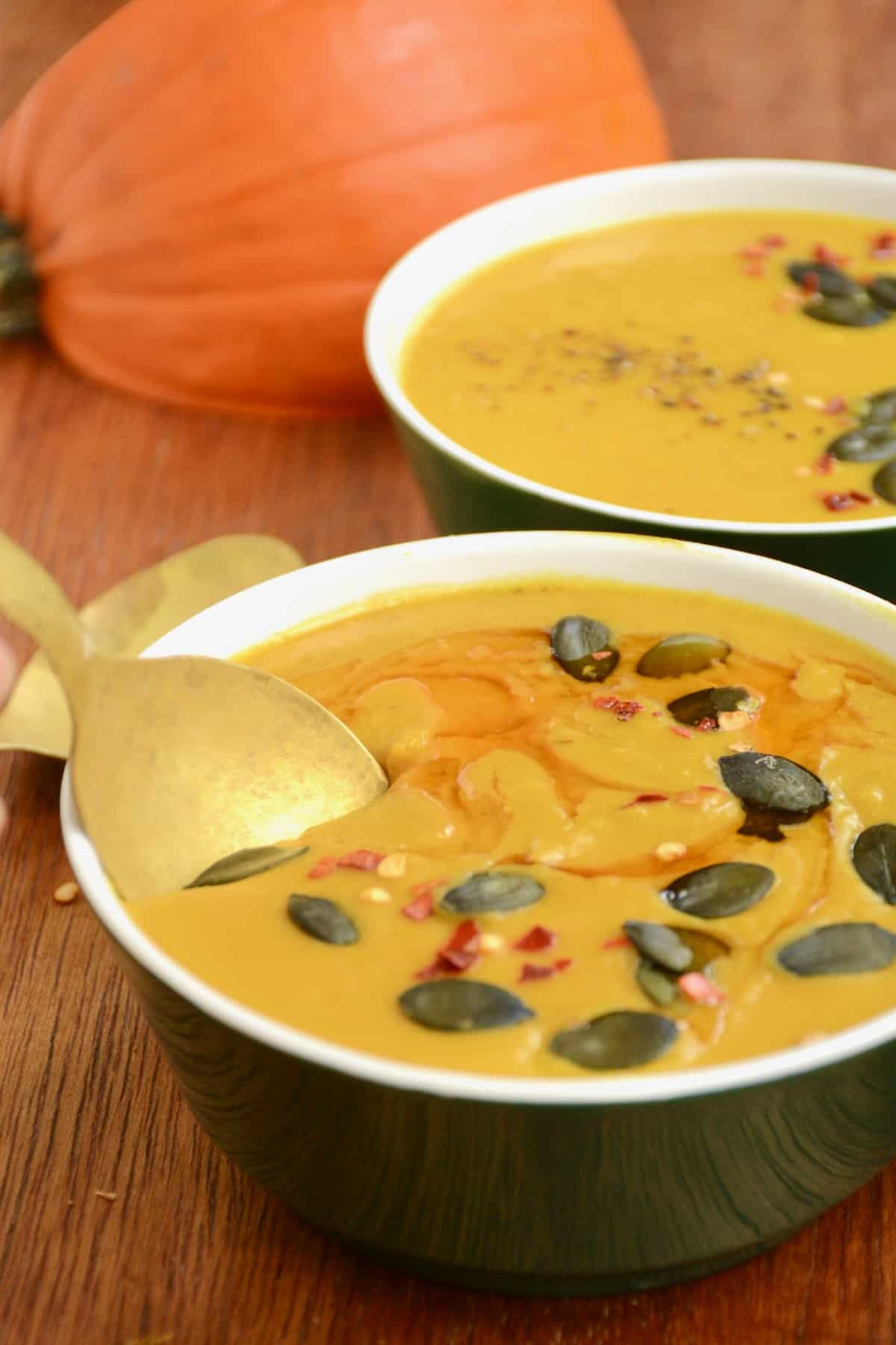 Dipping a spoon into the thick lentil pumpkin soup.