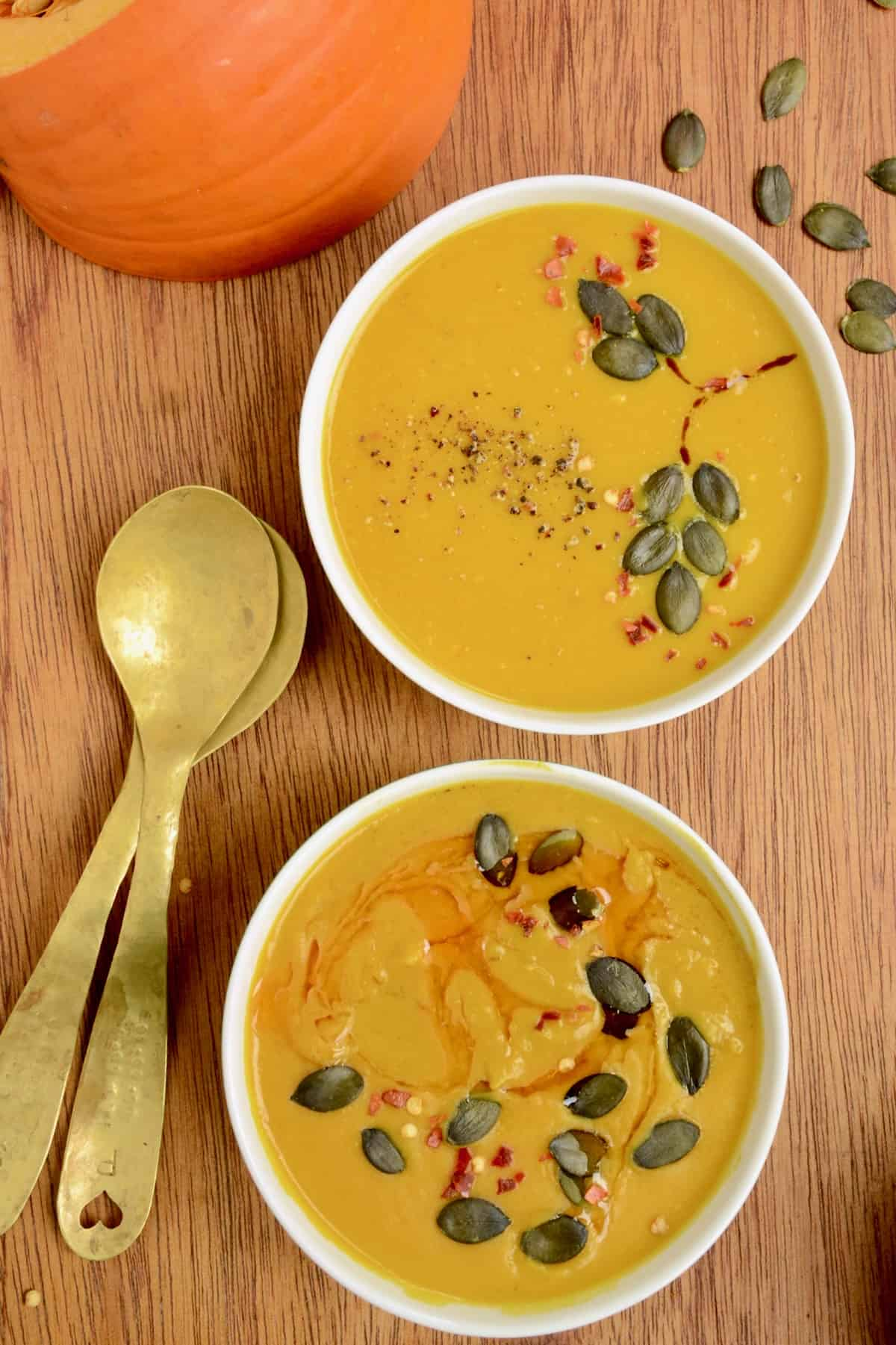 Two white bowls containing orange coloured soup, next to two brass spoons, and a wedge of pumpkin.