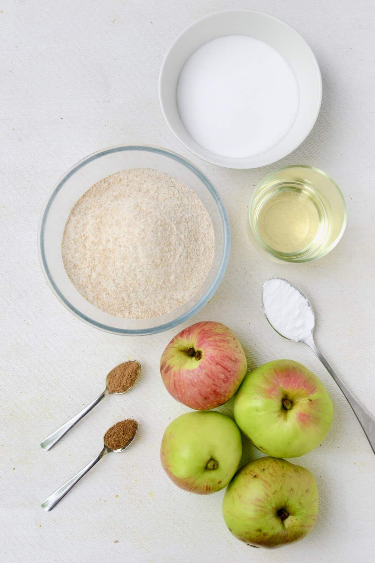 Ingredients for the vegan apple cake: Four apples, a bowl of flour, a bowl of sugar, oil, and spoonfuls of spices and baking soda on a white board.