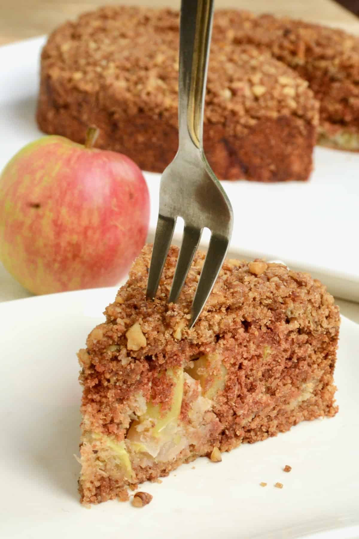 A fork digs in to a slice of apple cake.
