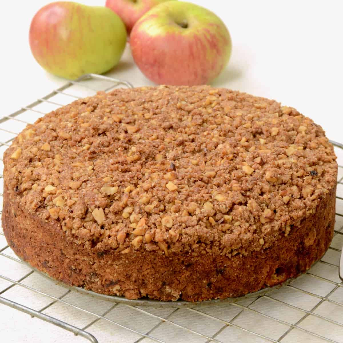 The vegan apple cake on a wire cooling rack, three apples in the background.