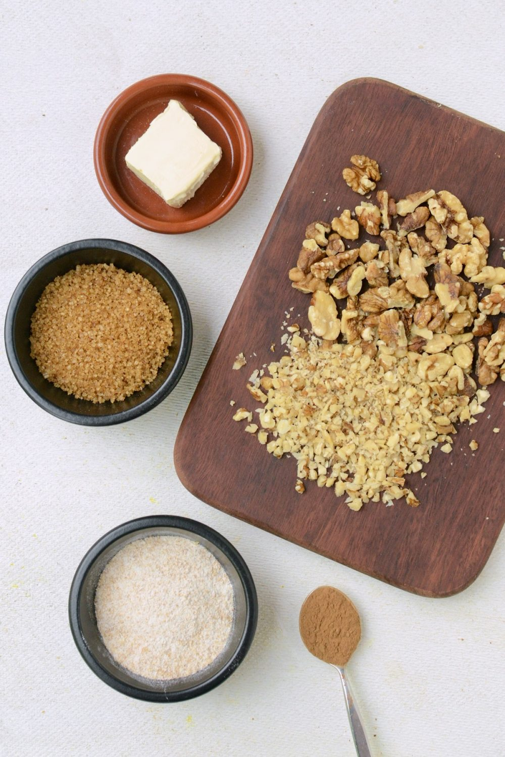 A wooden board with chooped walnuts, and small containers of vegan butter, demerara sugar, flour and cinnamon.