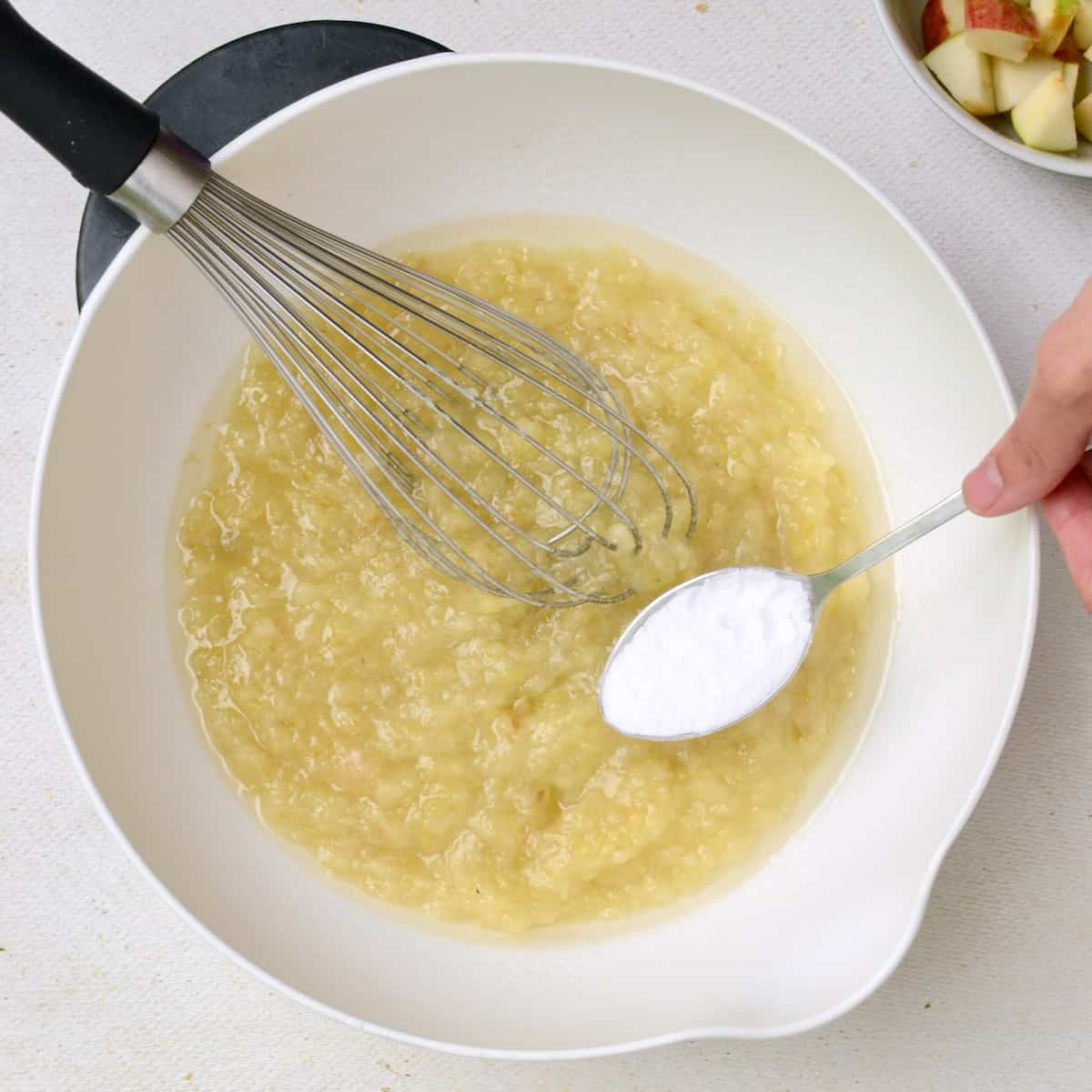 A mixing bowl containing apple, sugar and oil, with a spoonful of baking soda about to be added in.