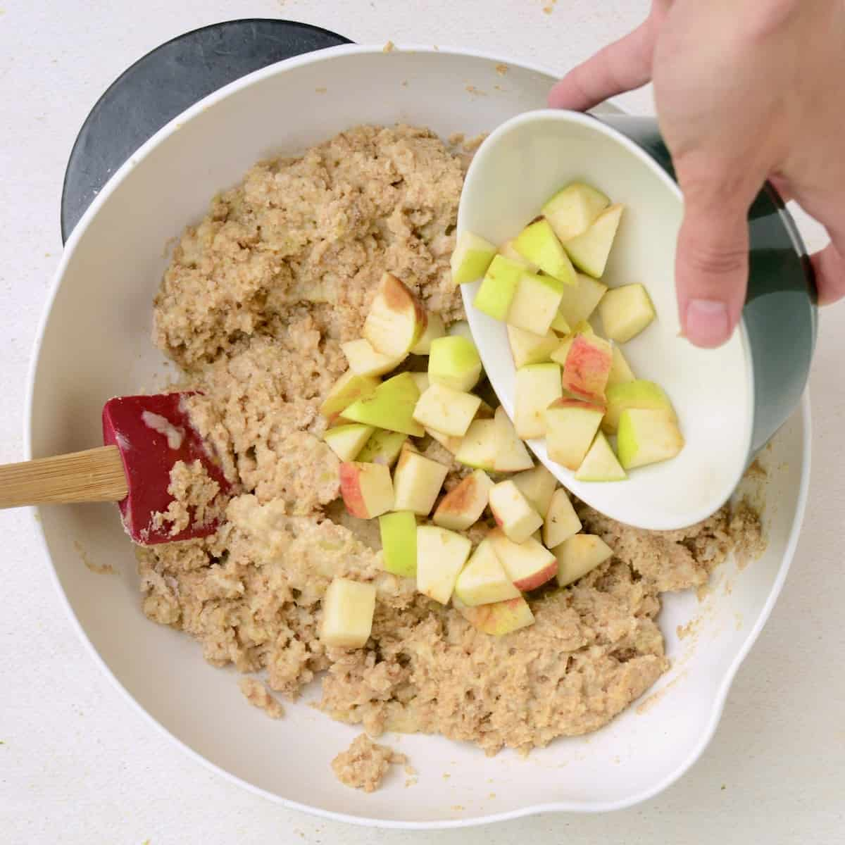 Adding the apple chunks into the cake batter.