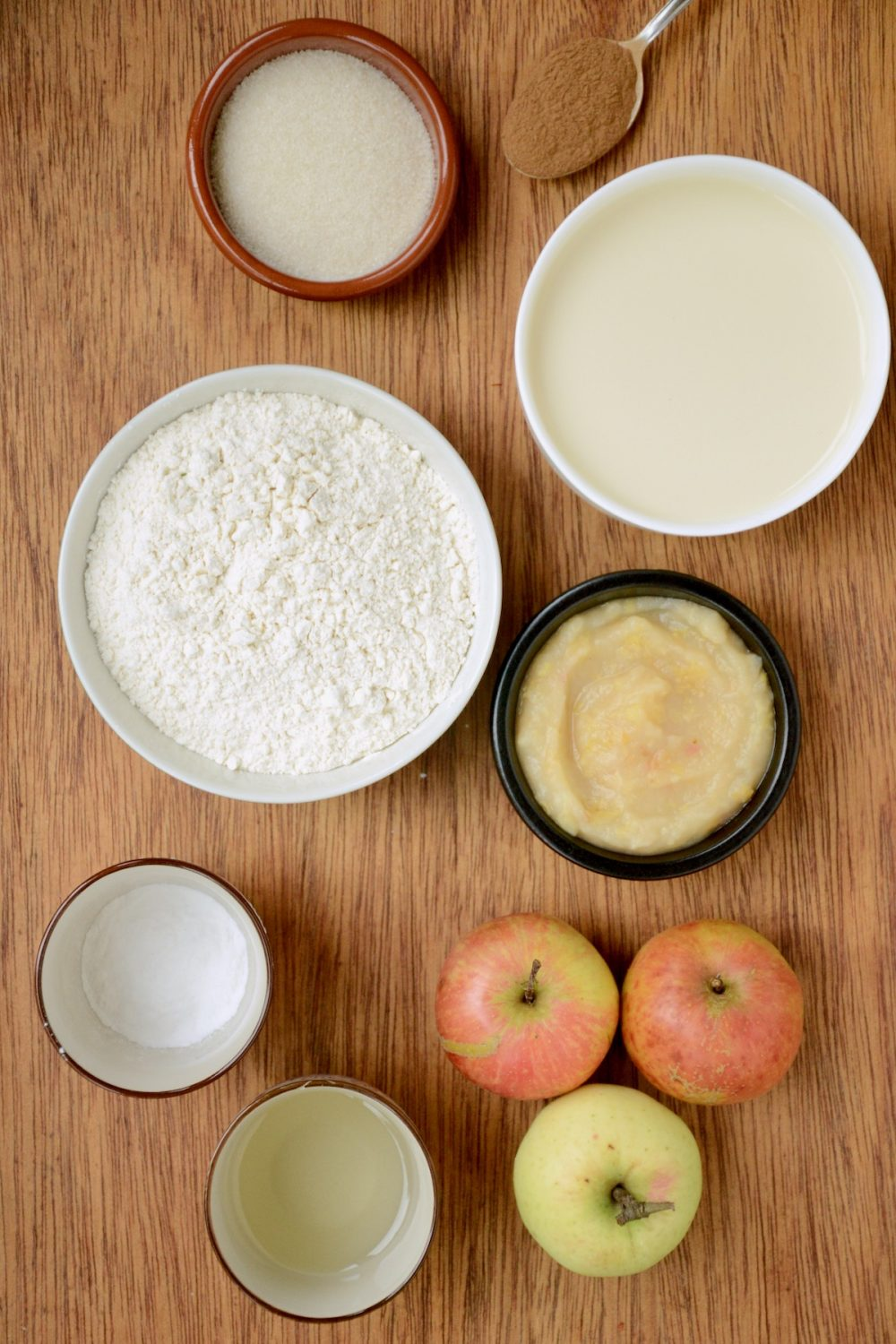 The ingredients laid out on a wooden board - bowls of flour, soy milk, applesauce, oil, baking powder, sugar, some apples and a spoonful of cinnamon.