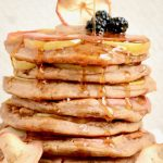 Golden maple syrup falls down the sides of the pancakes.