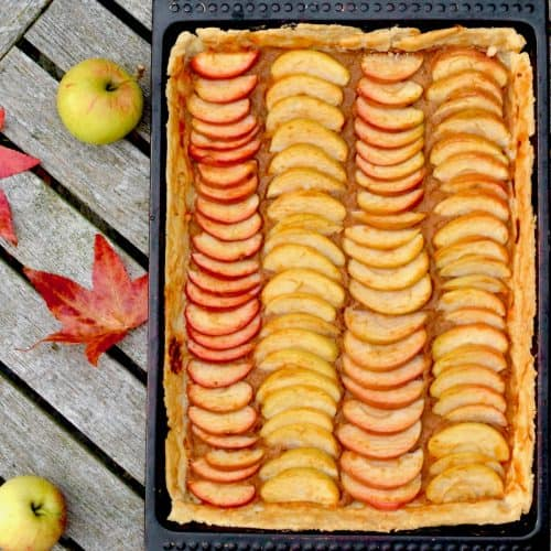 The rectangular apple tart on a table next to red autumn leaves and apples.
