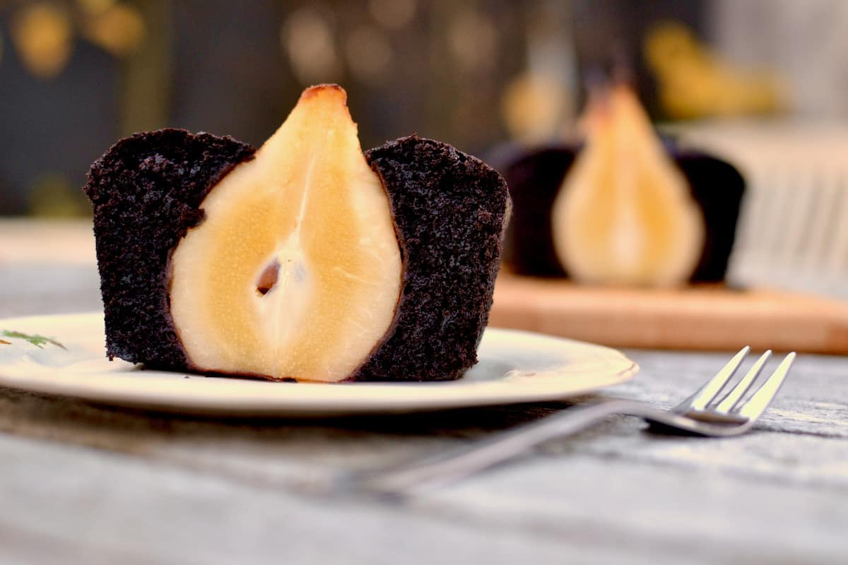 A slice of chocolate pear cake on a plate with the remaining cake blurred in the background.