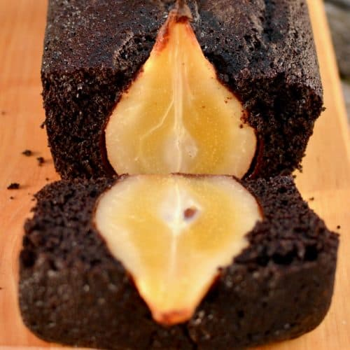 A chocolate pear cake with a slice cut reveals a whole pear baked inside.