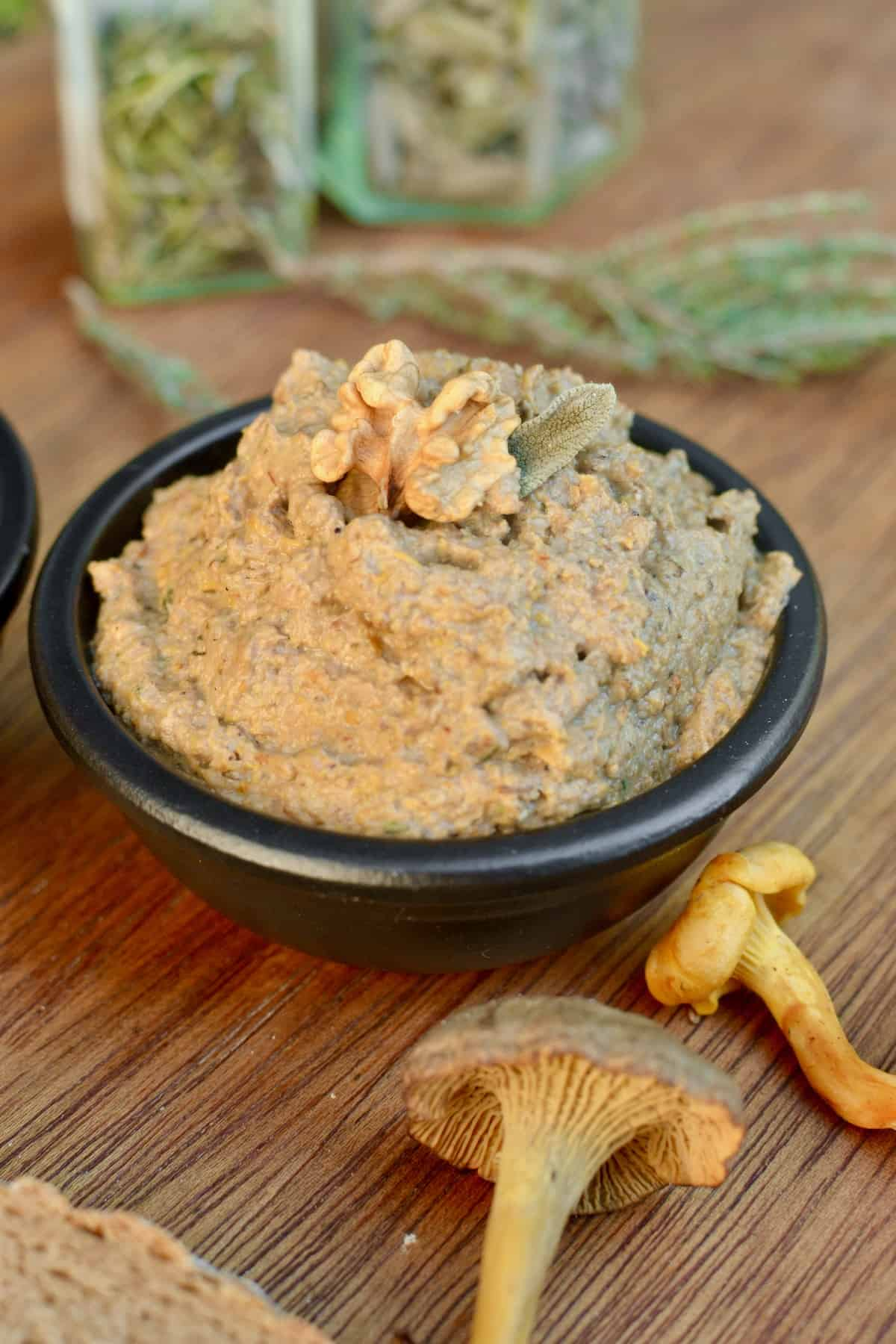 Light brown coloured mushroom pate topped with a walnut and sage leaf.
