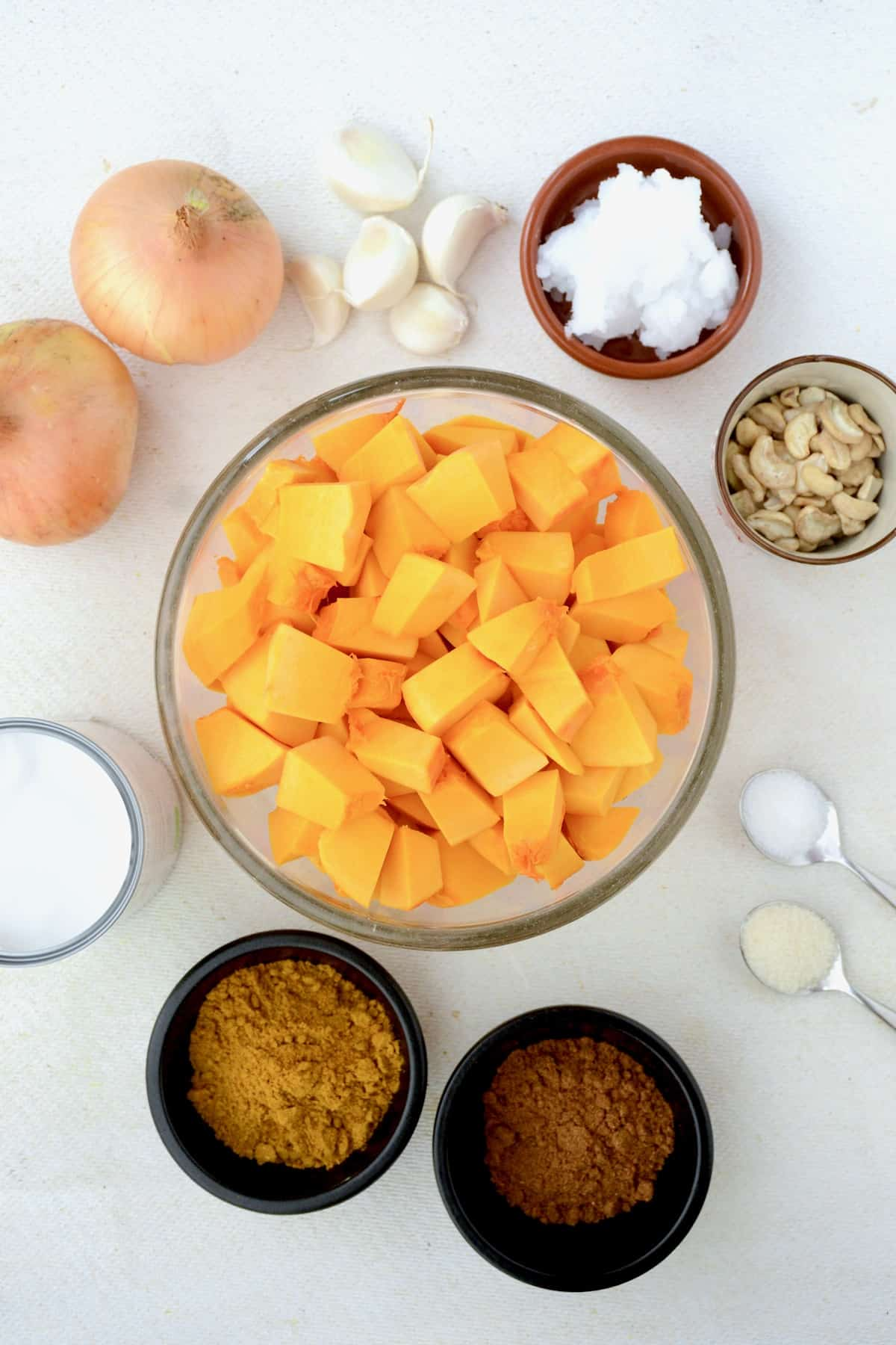 A bowl of pumpkin cubes, spices, onion, garlic, cashews, coconut oil and coconut milk on a white board.