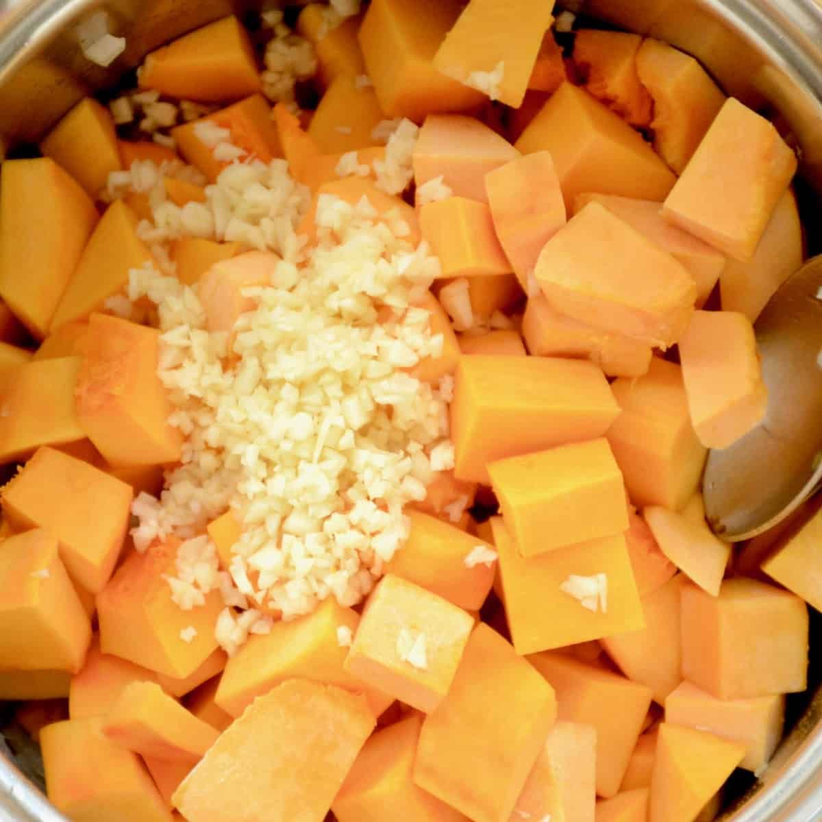 Finely chopped garlic on top of pumpkin cubes in a pan.
