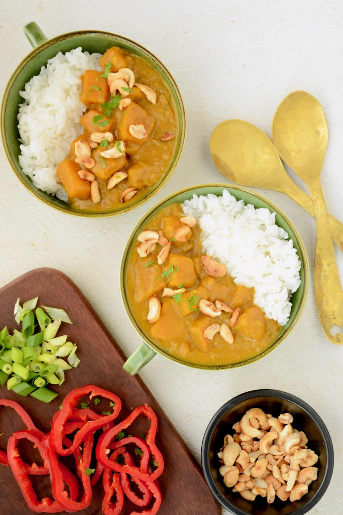 Two green bowls with curry and rice, next to a board of raw pepper and spring onions.
