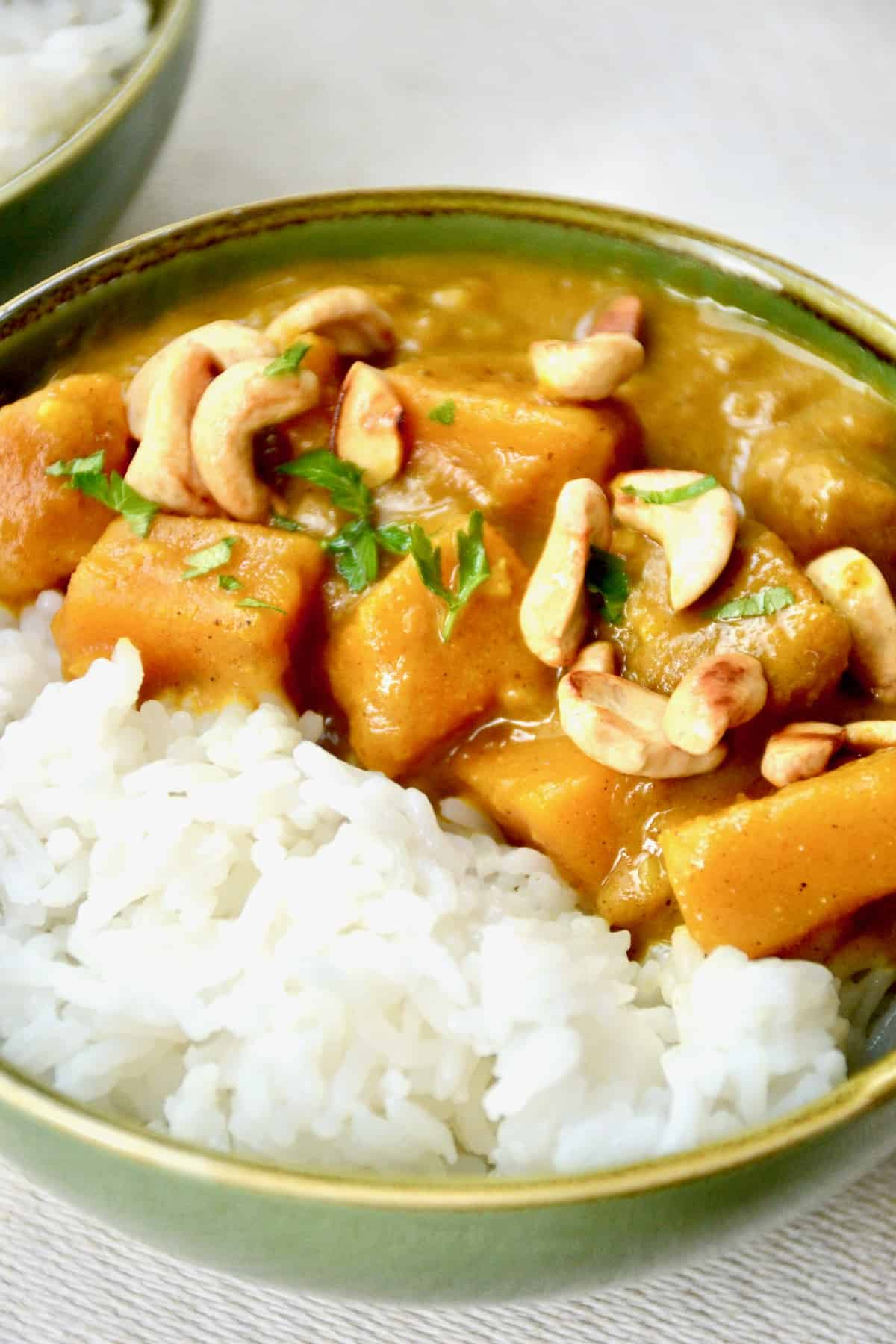 Cubes of pumpkin in a thick curry sauce, topped with cashews and served with white rice.