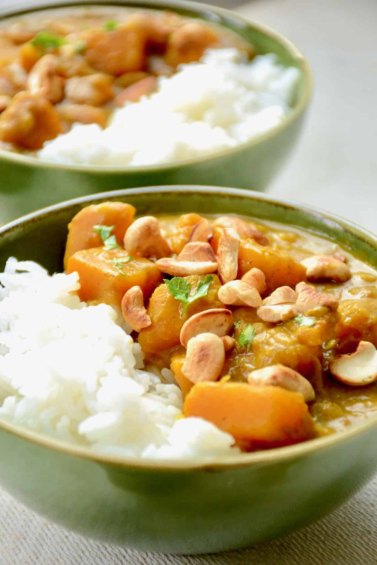 Two bowl of pumpkin curry with golden toasted cashews and sprinkling of herbs on top.